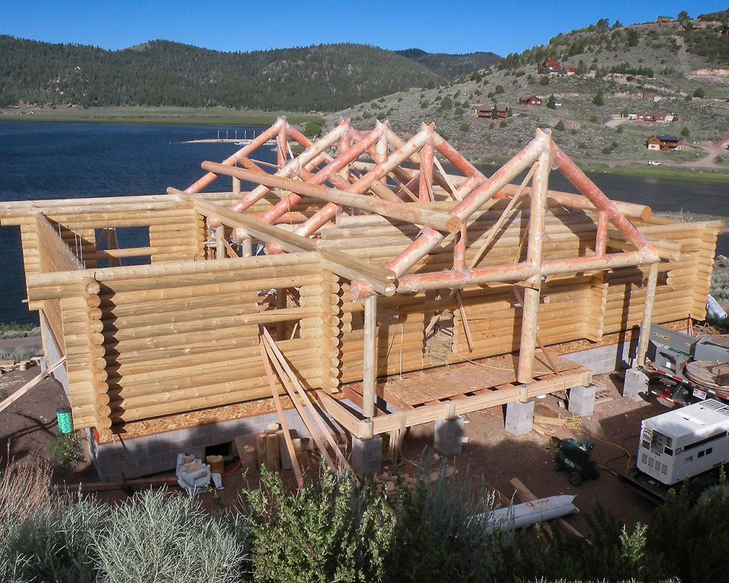 log truss roof being set on home by lake